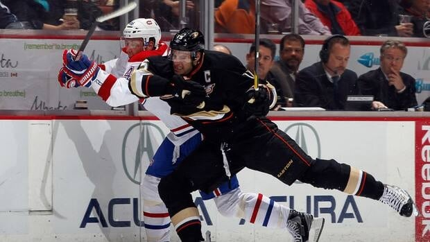 Ducks forward Ryan Getzlaf, front, checks Montreal's Andre Kostitsyn into the boards on Wednesday night in Anaheim, Calif.