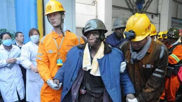 Rescued miners are helped out of a coal mine after being trapped underground for more than 36 hours at the Qianqiu Coal Mine in Sanmenxia City.