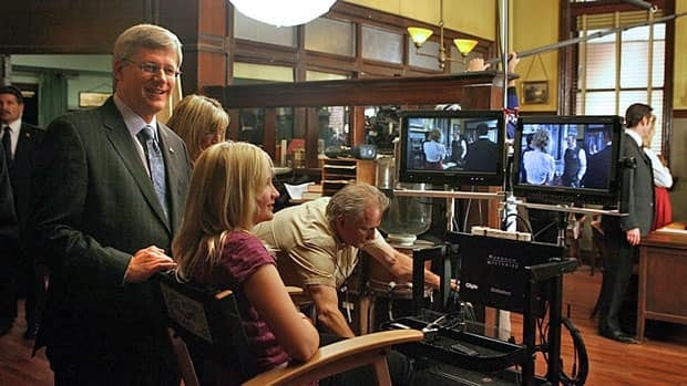 Prime Minister Stephen Harper, left, watches the taping of the Murdoch Mysteries with his daughter Rachel, seated, at studios in Toronto in October, 2010. Harper makes a cameo appearance on the Citytv series airing next week.