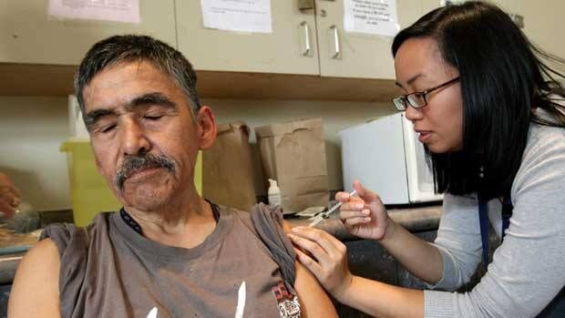 Rod Parnell, left, closes his eyes as he receives the H1N1 flu vaccine from a nurse at a clinic in Vancouver in 2009. Canada's new pandemic flu vaccine includes a main and backup supplier.
