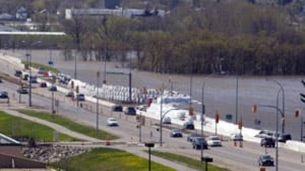 Motorists pass a wall of sandbags holding back the flood waters from the Assiniboine River on May 17, 2011 in Brandon. The province announced $27 million in upgrades to the city's flood protection systems Friday. (Ryan Remiorz/Canadian Press)