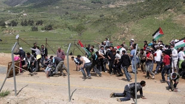 Arab demonstrators hold Palestinian flags as they approach the village of Majdal Shams in the Golan Heights on Sunday.