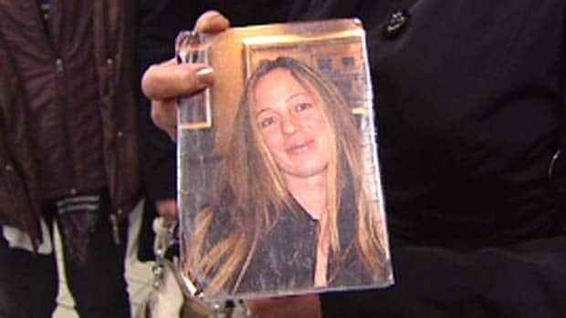 A photograph of Lisa Dudley is held by her mother following an RCMP code of conduct hearing in Vancouver in March.