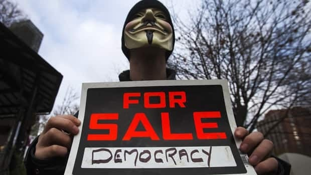 A masked protester holds a sign during the Occupy Toronto movement at St. James Park in Toronto. A Toronto judge decided to hold up the city's eviction notice on Monday.