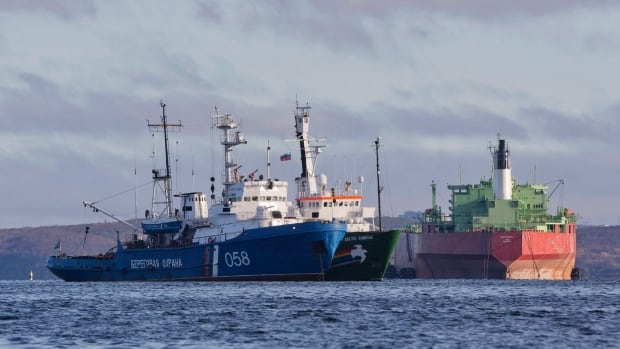 The Greenpeace ship Arctic Sunrise is anchored next to a Russian Coast Guard vessel near Murmansk Thursday. Russian investigators say they're considering fresh charges against 30 people from the ship who were detained last month for a protest against Arctic drilling.