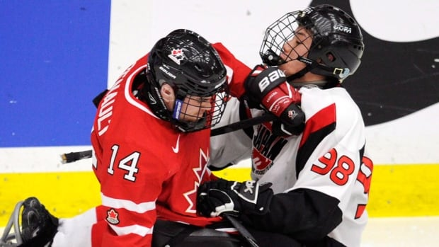 Canada's Steve Arseneault, left, collides with Japan's Yoshihiro Shioya during semifinal play at the 2012 World Sledge Hockey Challenge in Calgary. Toronto is hosting this year's event.