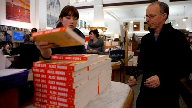 """Bookseller Taliah Lundstrom and co-worker David Bird stack copies of Alice Munro's latest book """"Dear Life,"""" at Munro's Books in Victoria, B.C., on Thursday, October 10, 2013 following the news that Canadian author Alice Munro won the Nobel prize for literature."""