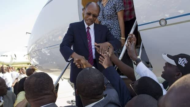 Former Haitian president Jean-Bertrand Aristide greets supporters after arriving at the airport in Port-au-Prince, Haiti, on Friday.