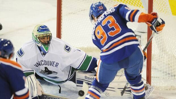 Edmonton Oilers' Ryan Nugent-Hopkins, right, scores on Vancouver Canucks goalie Roberto Luongo during the first period in Edmonton on Saturday.