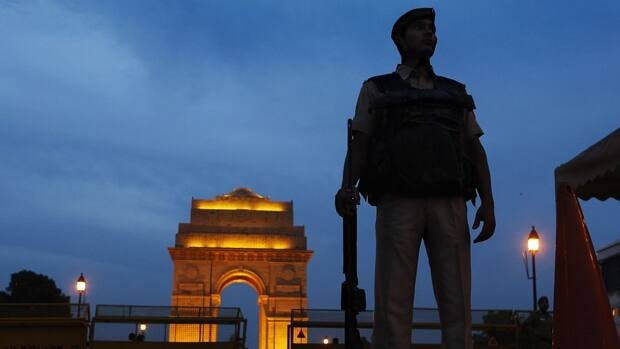 A policeman stands guard with the backdrop of the India Gate war memorial, a popular tourist place, in New Delhi, India, Thursday, July 14, 2011. Security across India is on high alert following the explosions in Mumbai on Wednesday.