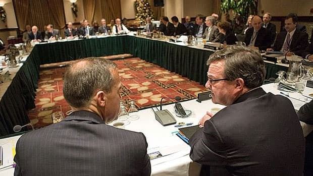 Federal Finance Minister Jim Flaherty, right, speaks to Bank of Canada governor Mark Carney prior to to a provincial, territorial and federal finance ministers meeting in Victoria Monday.