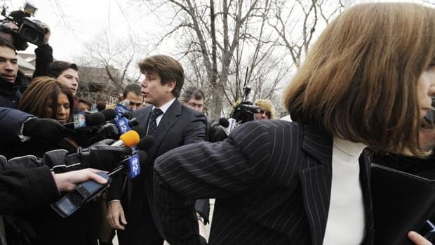 Former Illinois governor Rod Blagojevich tries to talk with the media but is led away by wife Patti, as they leave their home heading to Federal Court for his sentencing hearing in Chicago, Tuesday.