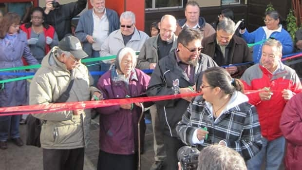 Eabametoong residents take part in cutting a ribbon for a new health centre. Chief Harry Papah (wearing black jacket in front, cutting ribbon) said many postive changes are happening in the First Nation community.