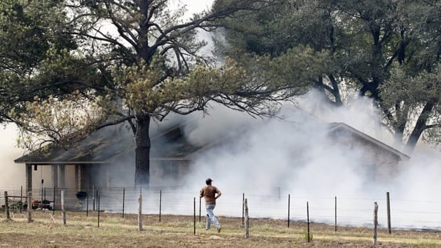 Smoke engulfs a house during a wildfire in central Texas on Monday.