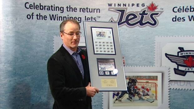 Jim Ludlow, president and CEO of True North Sports and Entertainment, holds up the Winnipeg Jets commemorative postage stamps at a news conference Thursday.