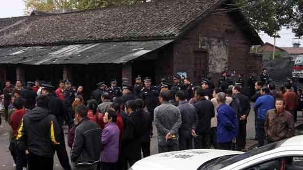 Relatives, onlookers and police officers gather near the state-owned Xialiuchong Coal Mine in Hengyang city on Sunday.