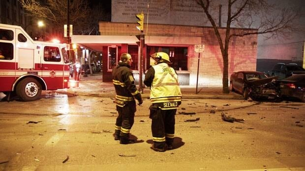 Firefighters stand at the intersection of King Street and McDermot Avenue, where an ambulance collided with a car. Nobody was hurt, according to police.