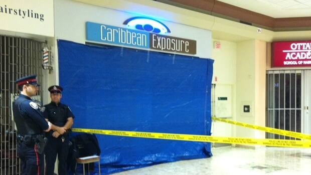 Caribbean Exposure tanning salon was still taped off and covered Thursday morning after two men were shot and killed inside Wednesday evening.