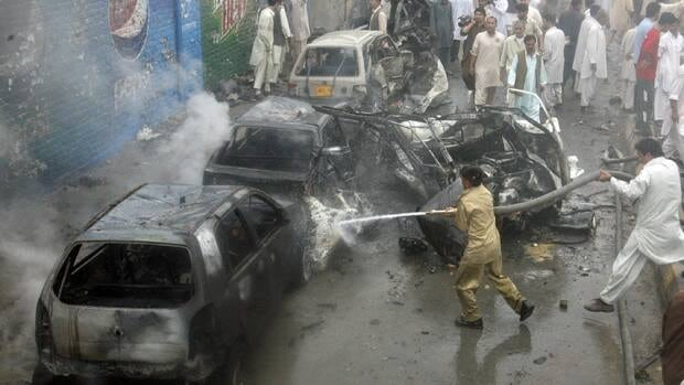 Firefighters spray water on damaged vehicles at the site of a car bomb blast in Quetta, Pakistan.