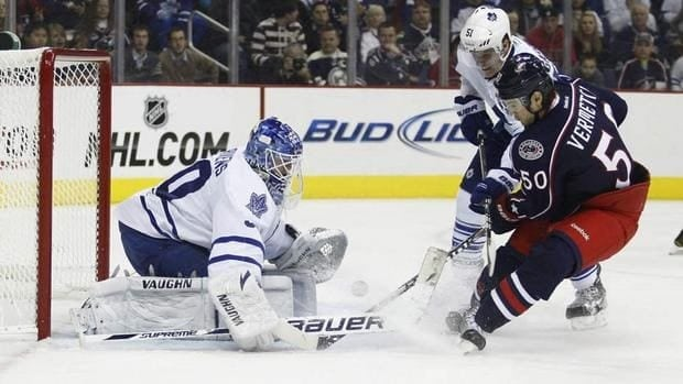 Leafs goalie Ben Scrivens, left, stops a shot by Blue Jackets forward Antoine Vermette, right, for one of his 38 saves on Thursday night.