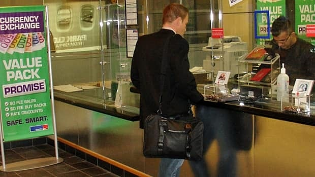 An employee serves a customer at a currency exchange outlet in Calgary. BMO predicts the loonie won't return to parity until the end of 2012.