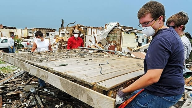 Lamar, Mo., residents move a porch into a debris pile Wednesday in Joplin, Mo., where doctors say three of the latest victims suffered from a rare fungal infection.