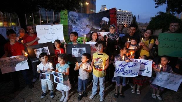 Syrian families and their children carry pictures of Syrian boy Hamza al-Khatib, who anti-government activists say was tortured and killed by Syrian security forces.