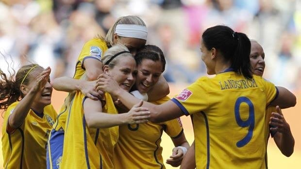 Sweden's Lisa Dahlkvist, front left, is mobbed by teammates after scoring against North Korea Saturday in Augsburg, Germany.