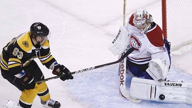 Boston Bruins forward Brad Marchand, left, watches as Montreal Canadiens goalie Carey Price makes a save during Game 1 action.