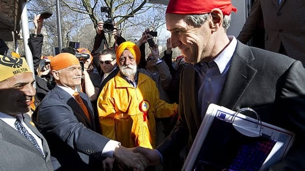 Liberal Leader Michael Ignatieff shakes hands with NDP Leader Jack Layton at a Khalsa Day celebration Sunday, April 24, 2011 in Toronto.