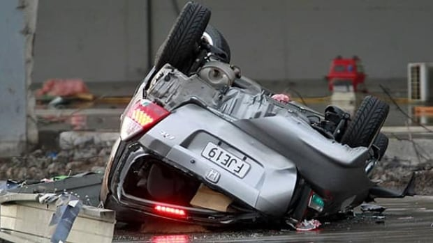 An upturned car is seen after a tornado ripped through the suburb of Albany in Auckland on Tuesday.