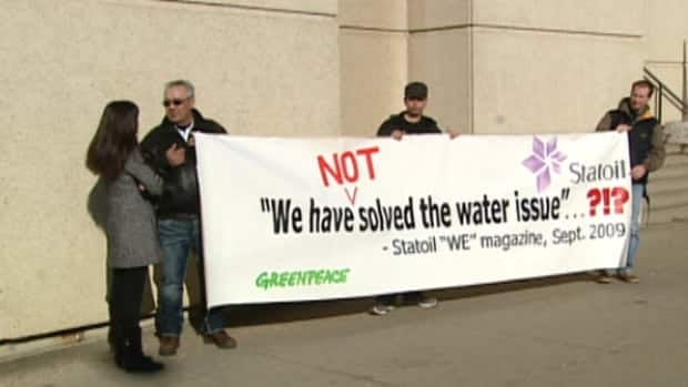 Protesters held a banner outside the Edmonton courthouse Wednesday.