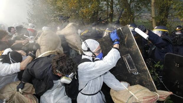 French police clash with anti-nuclear demonstrators in Lieusaint near Valognes on Wednesday as protesters try to enter on the tracks before the departure of the train convoy carrying nuclear waste.