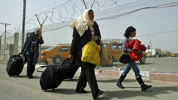 Palestinians carry their belongings after coming back from Egypt at the Rafah border crossing, southern Gaza Strip. Egypt's official news agency said Wednesday that the Rafah border crossing with Gaza will be permanently opened for Palestinians on Saturday.