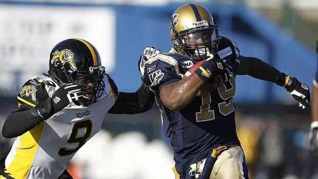 Tiger-Cats' linebacker Renauld Williams, left, tries to wrap up Blue Bombers running back Chris Garrett during the first half. Garrett ran for 190 yards and a touchdown.