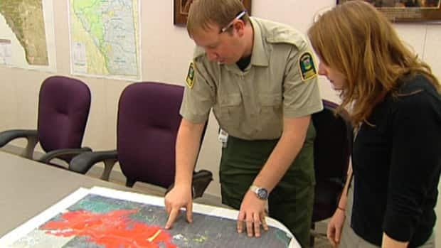 Geoffrey Driscoll with Alberta Sustainable Resource Development points to the Richardson Backcountry wildfire on a map.