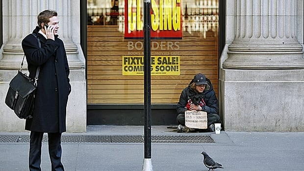 A business man and homeless person share a N.Y City sidewalk. The U.S. economy created no new jobs in August