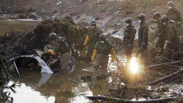Japanese Self-Defence Force members examine a submerged vehicle at Minamisoma, northeastern Japan, on Friday, three weeks after the powerful earthquake and tsunami struck.
