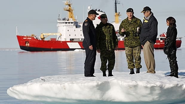 Prime Minister Stephen Harper talks with Gen. Walt Natynczyk, centre, while standing on an iceberg in Allen Bay in Resolute, Nunavut, in 2010. In the background is the Canadian Coast Guard icebreaker Henry Larsen.