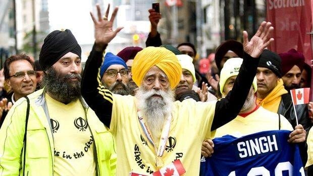 Fauja Singh, centre, celebrates at the finish line after completing the Scotiabank Toronto Waterfront Marathon on Oct. 16.