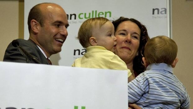 NDP MP Nathan Cullen, left, hands 14 month old twin son Elliot to his wife Diana as she already holds onto Isaac during a news conference in Vancouver, Friday. Cullen announced that he will seek the leadership of the federal NDP.