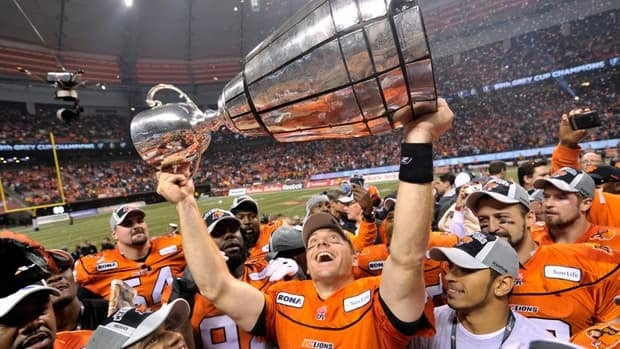 B.C. Lions quarterback Travis Lulay hoists the Grey Cup after beating the Winnipeg Blue Bombers 34-23 in the 99th CFL Grey Cup on Sunday in Vancouver.