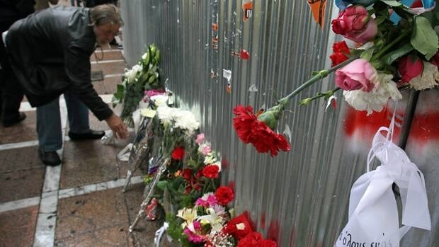 A man lays flowers Thursday outside the burnt hulk of a bank where three people died a year ago when the building was torched by anti-austerity rioters in Athens. S&P further downgraded Greece's debt Monday.