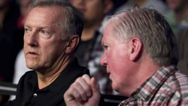 Maple Leafs general manager Brian Burke (right) and head coach Ron Wilson were likely not discussing the latter's new contract while they waited for a fight at the recent UFC event in Toronto.