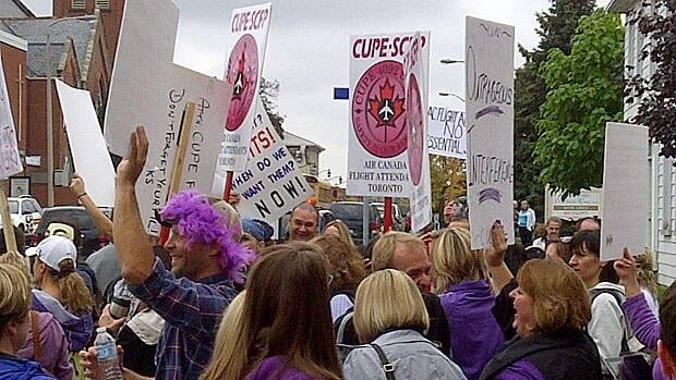 Dozens of Air Canada flight attendants rallied Thursday in front of Labour Minister Lisa Raitt's constituency office in Milton, Ont., some wearing masks and singing 'We're not gonna take it anymore.'