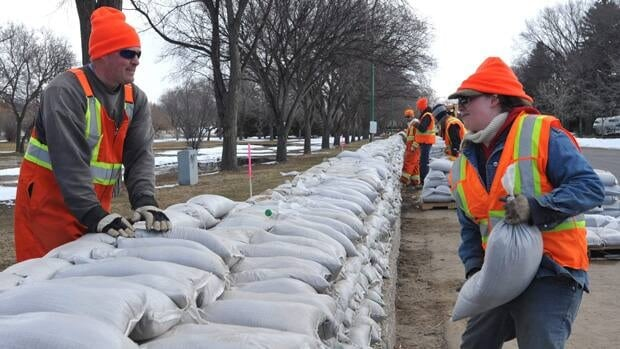City of Regina workers pile onto a dyke along the south side of Wascana Creek in Regina on Monday.