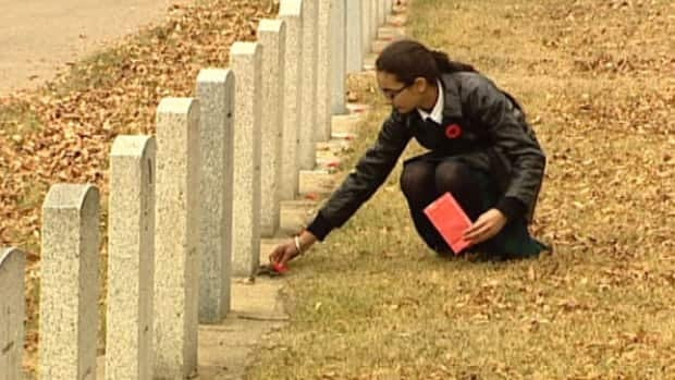Grade 8 student Manroop Randhawa lays a poppy on the grave of a soldier at Edmonton's Beechmount Cemetery Thursday.