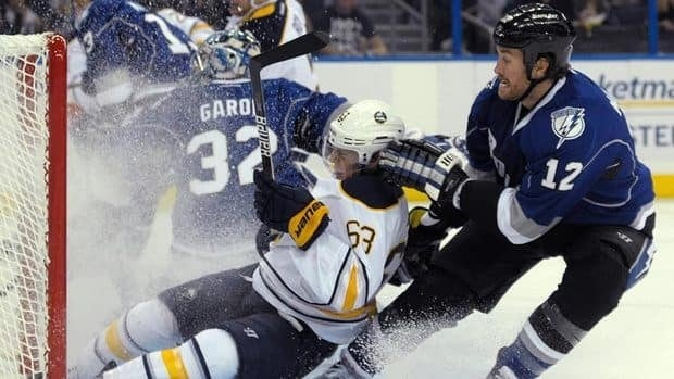 Buffalo Sabres left wing Tyler Ennis (No. 63) is bumped into the net by Tampa Bay Lightning's Ryan Malone, right, after missing on a shot past goalie Mathieu Garon (No. 32), during the first period of the Lighting's 3-0 victory over the Sabres.