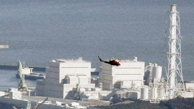 A helicopter flies past Japan's Fukushima Daiichi No.1 nuclear reactor on Saturday, where an explosion led to radiation leakage.