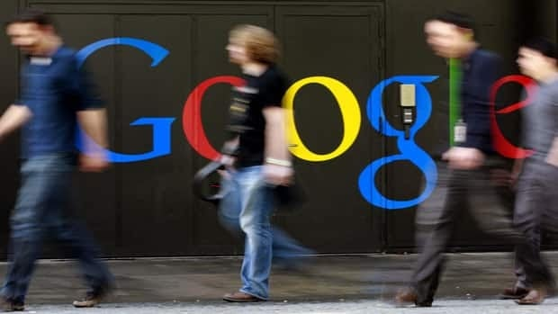 People walk past a logo next to the main entrance of the Google building in Zurich March 9.